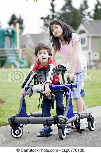 Hermana mayor ayudando al hermano menor discapacitado en Walker - csp6776180