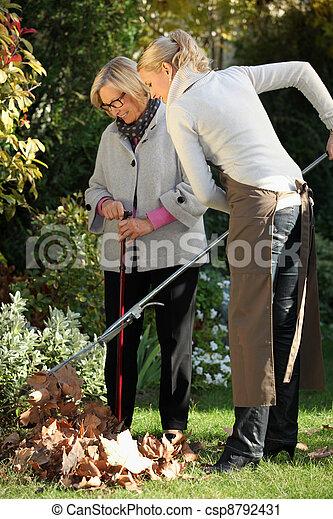 Una joven ayudando a una anciana a hacer jardinería - csp8792431