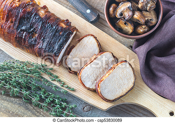 Pork loin wrapped in bacon with roasted mushrooms - csp53830089