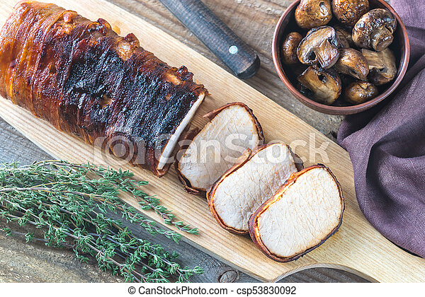 Pork loin wrapped in bacon with roasted mushrooms - csp53830092