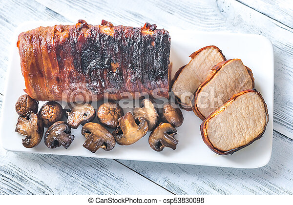Pork loin wrapped in bacon with roasted mushrooms - csp53830098