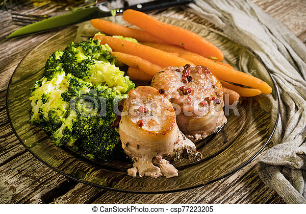 Pork tenderloin wrapped in bacon. - csp77223205