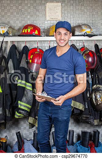 Bombero seguro sosteniendo portapapeles en la estación de bomberos - csp29674770