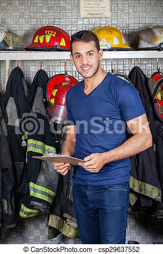 Bombero sonriente sosteniendo portapapeles en la estación de bomberos - csp29637552