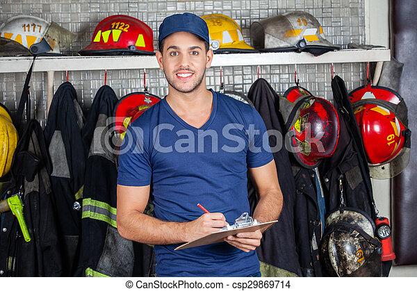 Un trabajador seguro sosteniendo portapapeles en la estación de bomberos - csp29869714