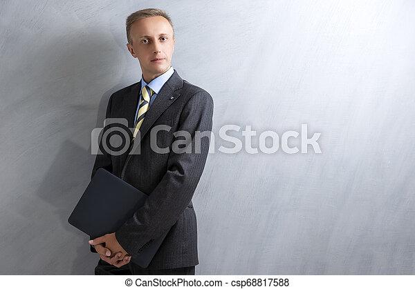 Portarit de joven caucásico en traje gris posando con portátil contra pared grunge. - csp68817588
