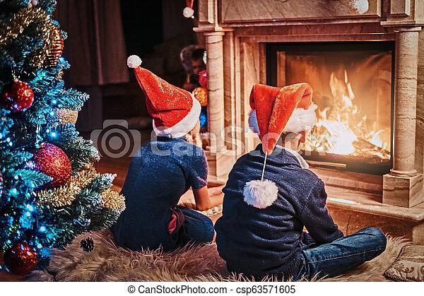 porter, vivant, soeur, salle, chapeaux, dos, santa, frère, noël., vue, décoré, suivant, cheminée, chauffage - csp63571605