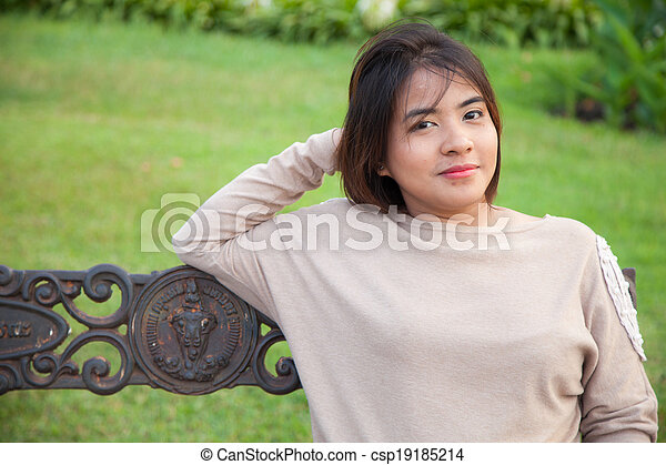 Portrait Asian woman sitting on the bench. - csp19185214