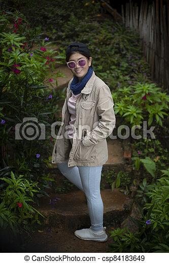 portrait beautiful asian woman standing in garden - csp84183649