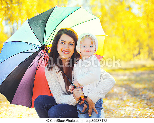 Portrait happy smiling mother and child with umbrella walking in autumn day - csp39937172