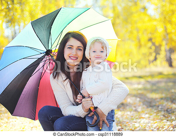 Portrait happy smiling mother and child with umbrella walking in autumn park - csp31118889
