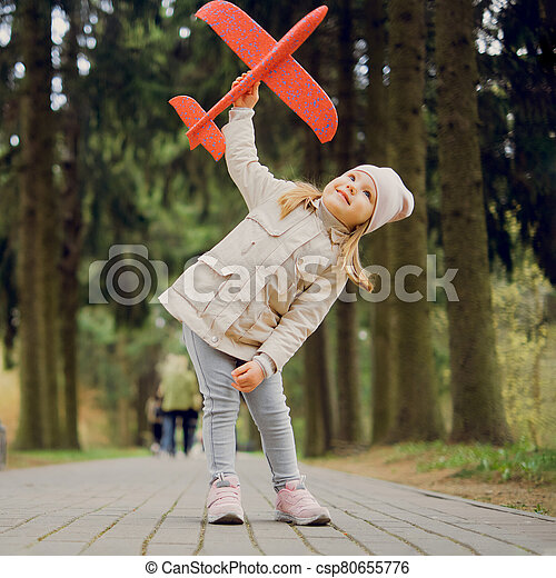 portrait of 3 years old girl with a toy airplane in her hands in the park - csp80655776