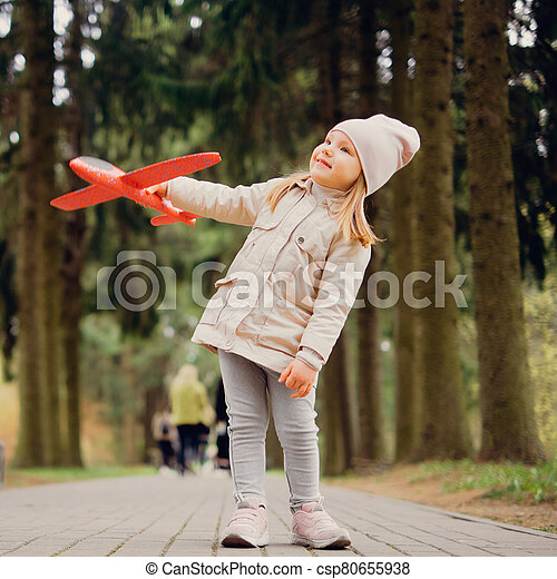 portrait of 3 years old girl with a toy airplane in her hands in the park - csp80655938