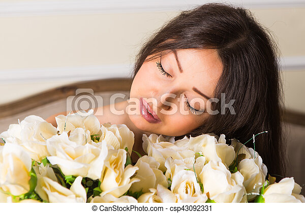 portrait of a beautiful brunette girl with a bouquet of roses - csp43092331