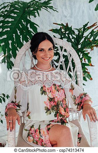 Portrait of a beautiful brunette woman in green plants - csp74313474