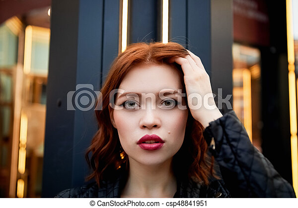 Portrait of a beautiful redhead. Fiery hair and full lips. Walking around the city - csp48841951