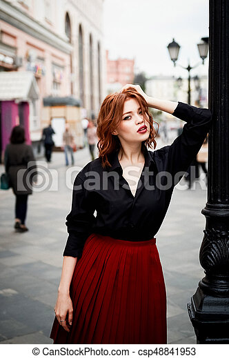Portrait of a beautiful redhead. Fiery hair and full lips. Walking around the city - csp48841953