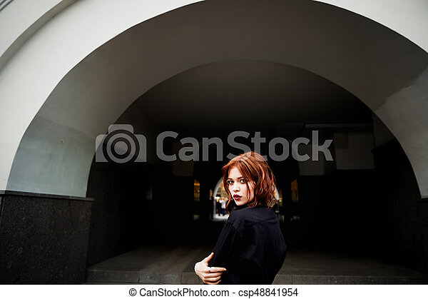 Portrait of a beautiful redhead. Fiery hair and full lips. Walking around the city - csp48841954