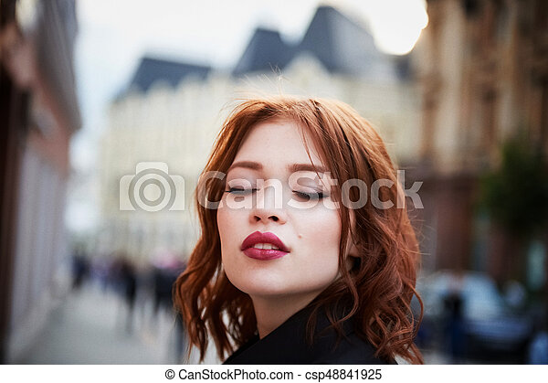 Portrait of a beautiful redhead. Fiery hair and full lips. Walking around the city - csp48841925