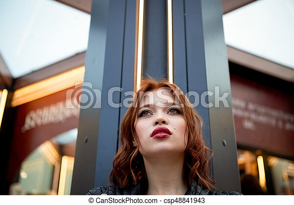 Portrait of a beautiful redhead. Fiery hair and full lips. Walking around the city - csp48841943