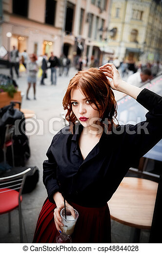 Portrait of a beautiful redhead. Fiery hair and full lips. Walking around the city - csp48844028