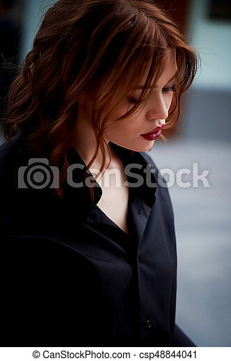 Portrait of a beautiful redhead. Fiery hair and full lips. Walking around the city - csp48844041