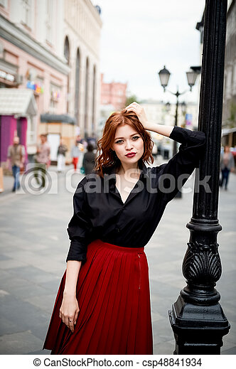 Portrait of a beautiful redhead. Fiery hair and full lips. Walking around the city - csp48841934