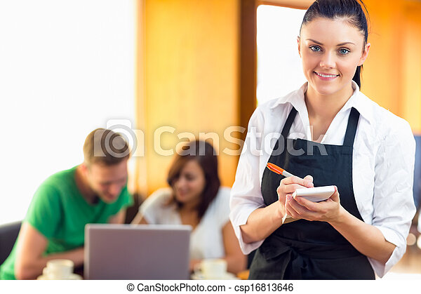 Portrait of a beautiful waitress writing an order with two students using laptop at the coffee shop - csp16813646