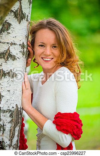 portrait of a beautiful woman in spring park near birch - csp23996227