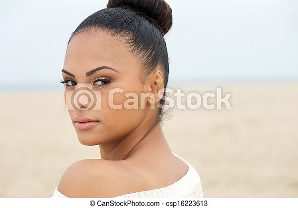 Portrait of a beautiful woman looking over shoulder - csp16223613