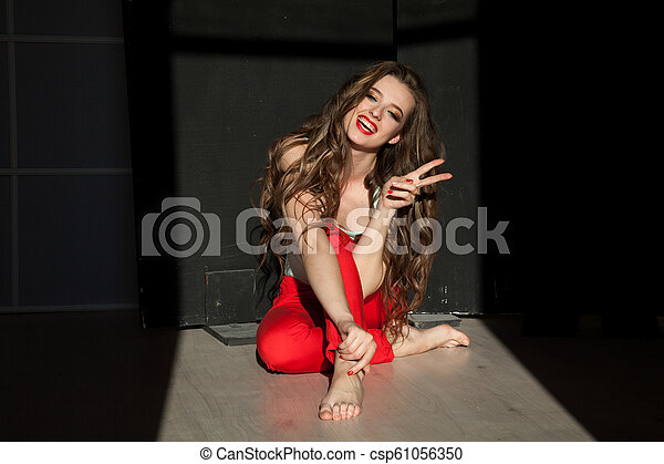 Portrait of a beautiful woman sitting on the floor - csp61056350