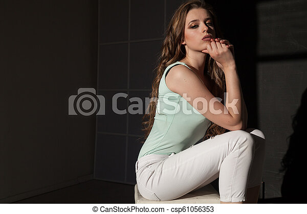 Portrait of a beautiful woman sitting on the floor - csp61056353