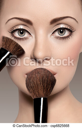 Portrait of a beautiful woman with a make up brush - csp6825668