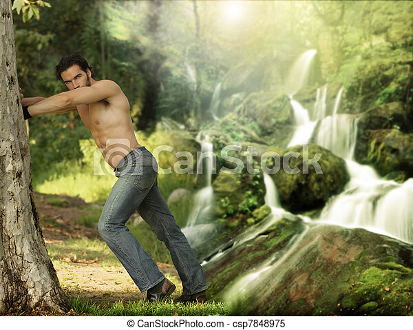 Portrait of a beautiful young muscular man leaning against a tree in a beautiful, heavenly place - csp7848975