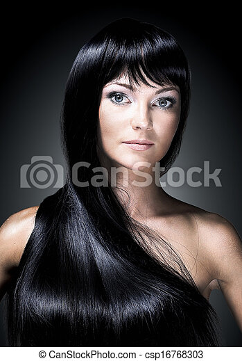 Portrait of a beautiful young woman with elegant long shiny hair. Isolated on black background - csp16768303