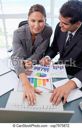 Portrait of a business team studying statistics with a laptop - csp7975872