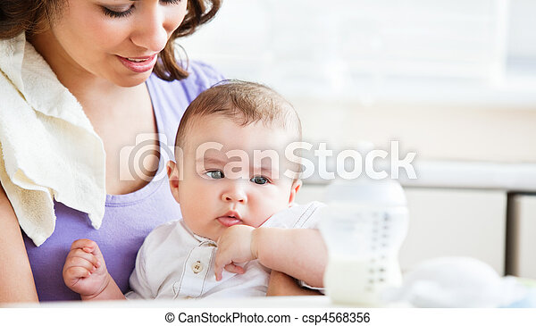 Portrait of a charming mother taking care of her adorable baby in the kitchen at home - csp4568356