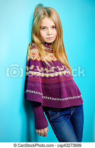 Portrait of a cute 7 year old girl wearing knitted clothes posing over bright blue background. - csp43273699