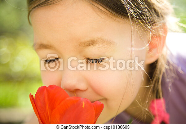 Portrait of a cute little girl smelling flowers - csp10130603