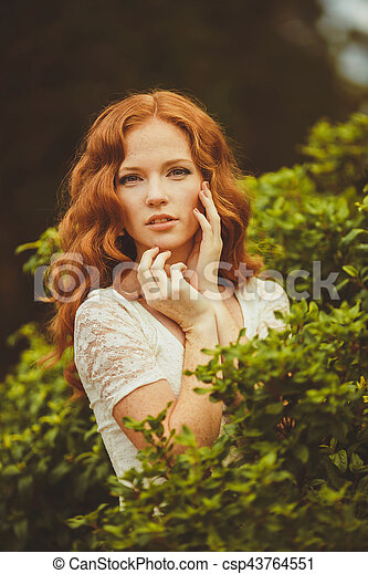 portrait of a cute redhaired young woman in the park