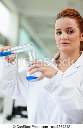 Portrait of a cute scientist pouring blue liquid in an Erlenmeyer flask in a laboratory - csp7364212