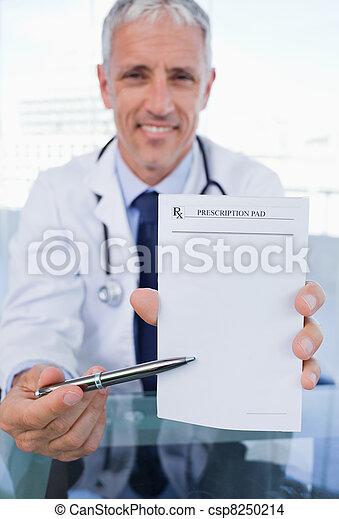 Portrait of a doctor showing a blank prescription sheet - csp8250214