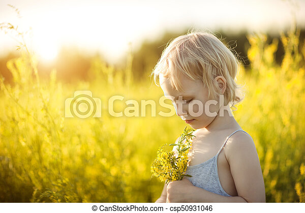 Portrait of a girl in a field with yellow flowers - csp50931046