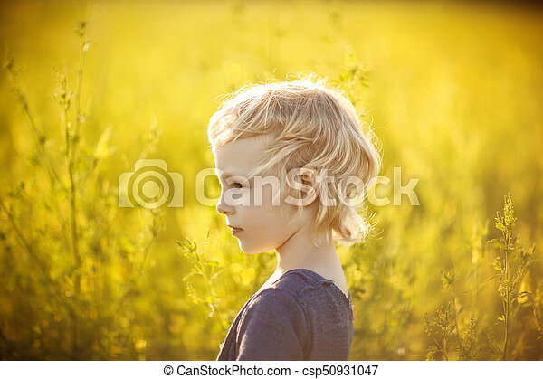 Portrait of a girl in a field with yellow flowers - csp50931047