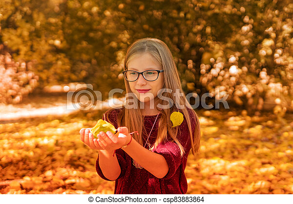 portrait of a girl with autumn leaves - csp83883864