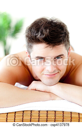 Portrait of a handsome man lying on a massage table smiling at the camera in a spa center - csp4137978