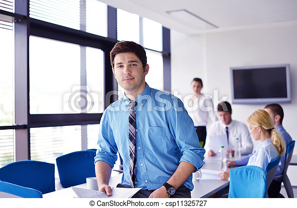 Portrait of a handsome young  business man  on a meeting in offce with colleagues in background - csp11325727
