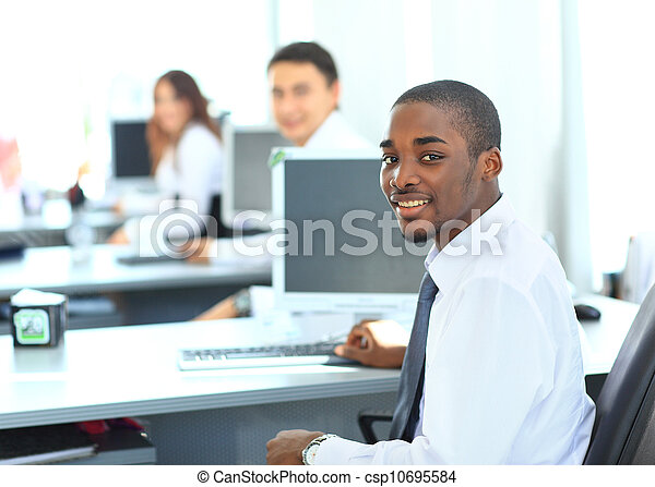 Portrait of a happy African American entrepreneur displaying computer laptop in office - csp10695584