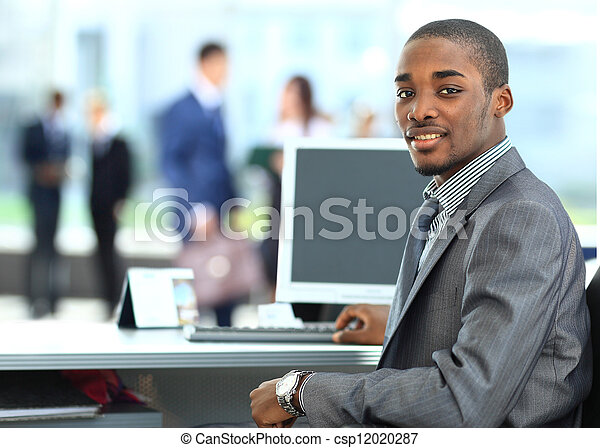 Portrait of a happy African American entrepreneur displaying computer laptop in office - csp12020287