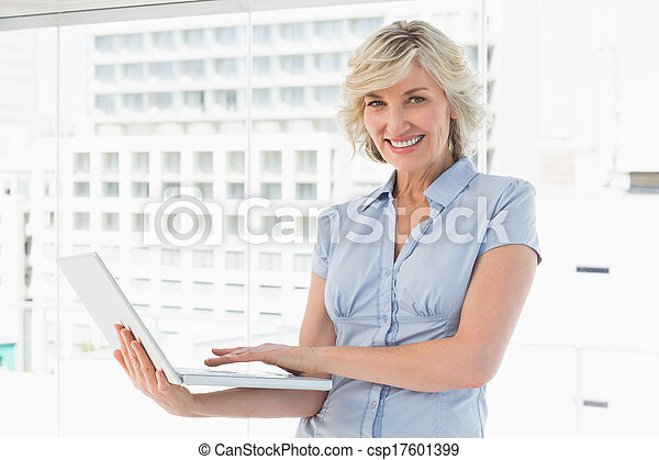 Portrait of a happy businesswoman using laptop - csp17601399